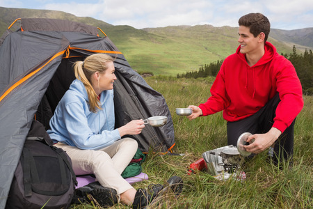 Happy couple cooking outdoors on camping trip in the countryside photo