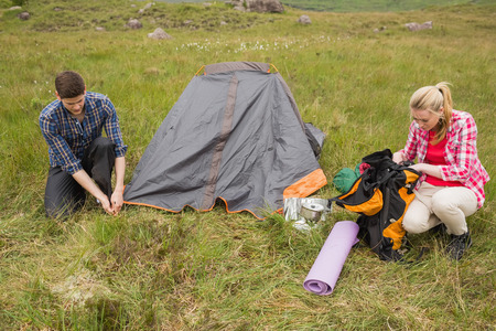 pitching: Couple pitching their tent in the countryside