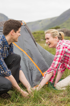 pitching: Smiling couple pitching their tent together in the countryside
