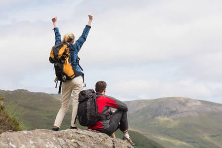 Excited couple reaching the top of their hike and admiring the mountain view photo