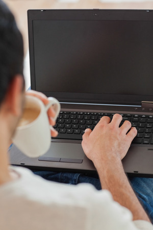 over the shoulder view: Over shoulder view of young man using his laptop in bright living room Stock Photo