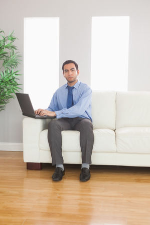 Stern young businessman using his laptop while sitting on cosy sofa in bright living room photo