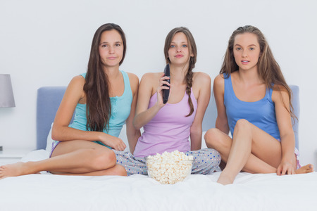 sleepover: Girls sitting on bed at sleepover with popcorn and looking at camera Stock Photo