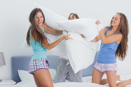 pijamada: Amigos que tienen lucha de almohadas en casa en el partido de sueño