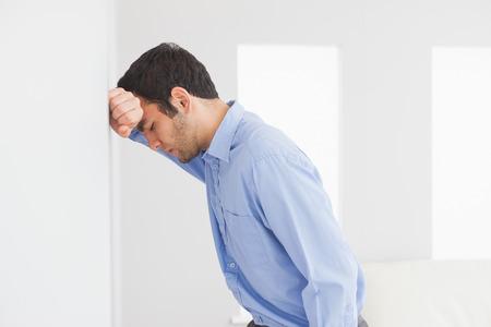 decepcionado: Hombre triste con el pu�o cerrado apoyando su cabeza contra una pared Foto de archivo