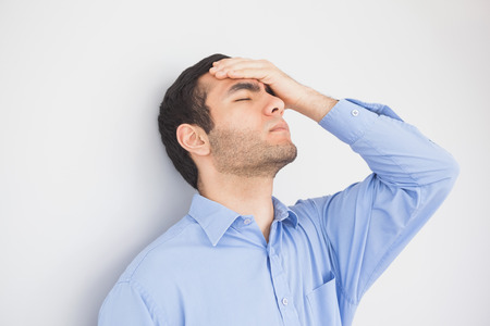 wistfulness: Irritated man with eyes closed and hand on the forehead leaning against a wall Stock Photo