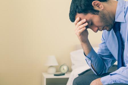自宅の寝室で彼のベッドの上の手で頭を座っている悲しい男