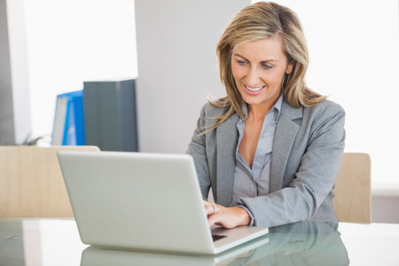 woman laptop: A smiling blonde businesswoman typing on a laptop in an office