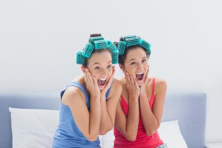 pijamada: Amigos con los rodillos del pelo en sentado en la cama y gritando a fiesta de pijamas