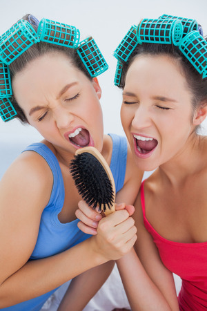 Friends in hair rollers holding hairbrush having fun and singing at sleepover photo