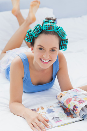 Girl in hair rollers lying in bed and smiling in camera reading magazine photo