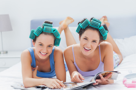 Girls in hair rollers holding magazines and smiling at camera at sleepover photo