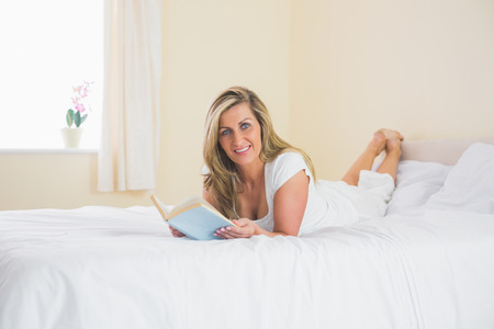 Content mature blonde woman looking at camera and reading a novel lying on her bed in a bedroom photo