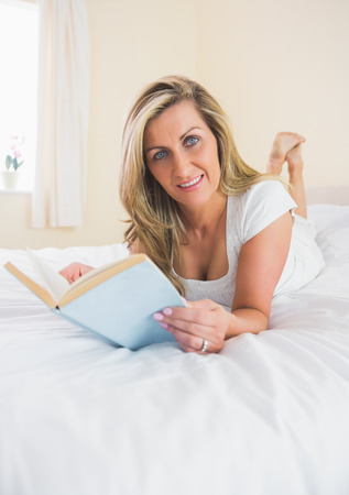 Pleased mature blonde woman looking at camera reading a book lying on her bed in a bedroom photo