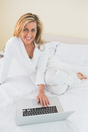 Smiling mature blonde woman using a laptop lying on her bed in a bedroom photo