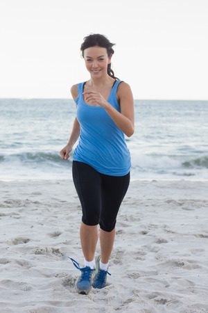 Sporty woman running at the beach in front of the ocean photo