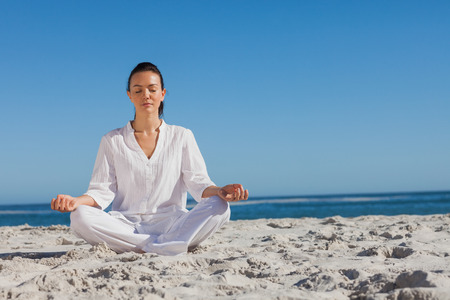 escapism: Attractive young blonde woman dressed all in white doing yoga on a beach