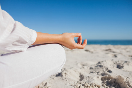 Close up view of womans hand in yoga pose at beach photo