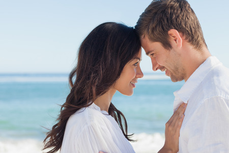 long hair man: Attractive couple embracing on the beach on a sunny day Stock Photo