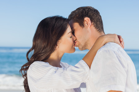 facing away: Couple embracing and kissing each other on the beach against ocean Stock Photo