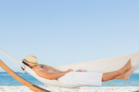 Man wearing straw hat relaxing in a hammock on the beach on holidays photo