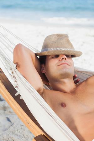 Man wearing straw hat lying in hammock and sleeping on holidays photo