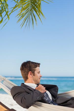 undoing: Businessman lying in hammock against ocean at the beach Stock Photo