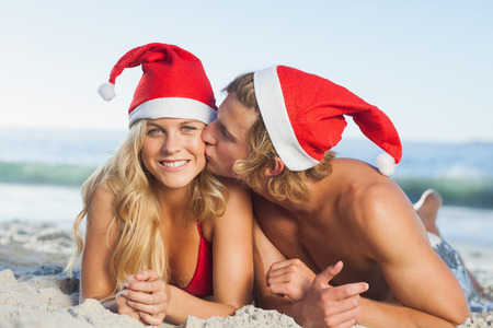 Man giving kiss to partner wearing christmas has on beach photo