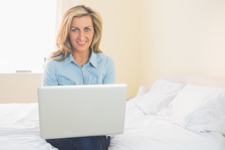 Pleased mature blonde woman sitting on a bed using a laptop in a bedroom photo