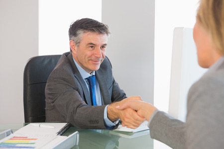 Pleased mature businessman shaking the hand of a blonde interviewee in office photo