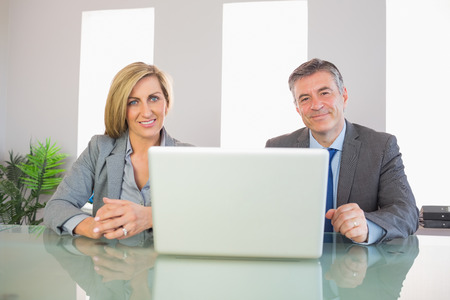 Two smiling mature business people looking at camera behind an opened laptop at office photo