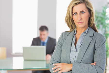 Unsmiling blonde businesswoman looking at camera crossed arms with a mature businessman working on laptop on background at office  photo