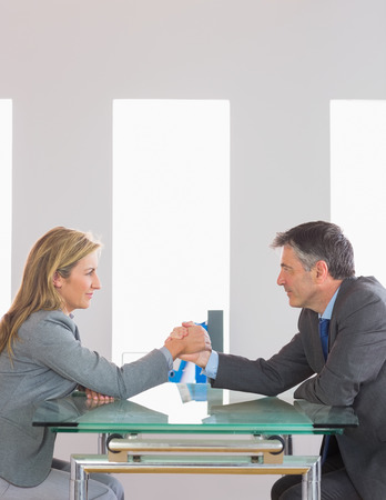 Two content mature businesspeople having an arm wrestling sitting around a table at office photo