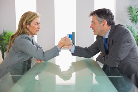 Two irritated mature businesspeople having an arm wrestling sitting around a table at office photo