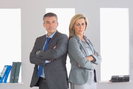 Two unsmiling mature businesspeople looking seriously at camera standing firmly back to back with crossed arms at office photo
