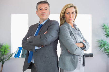 Two serious mature businesspeople looking at camera standing firmly back to back with crossed arms at office photo