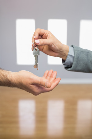 letting: Realtor giving house key to buyer in empty room Stock Photo