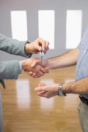 Close up of a man receiving a handshake and a key at the same time in a room photo