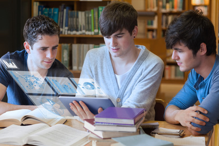 Serious students working on their digital tablet in university library photo