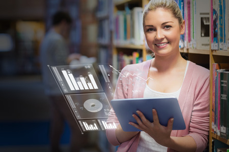 Cheerful student analysing figures on her futuristic tablet in university library photo
