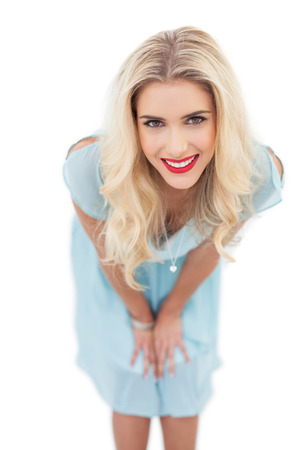 Happy blonde model in blue dress posing hands on the thighs on white background photo