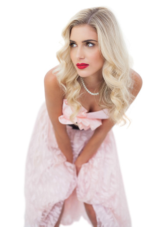Thinking blonde model in pink dress posing hands on the thighs on white background photo