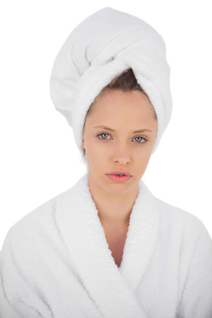 Serious brunette in bathrobe looking at camera on white background photo