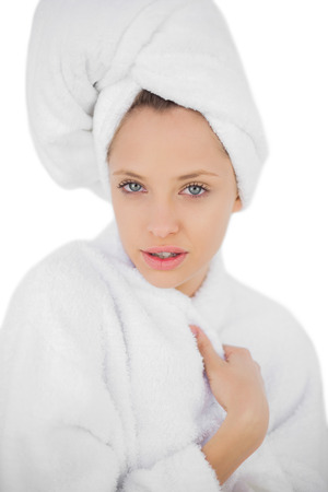 Pleased brunette in bathrobe looking at camera on white background photo