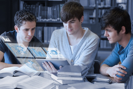 Serious students working on their digital tablet pc in university library photo