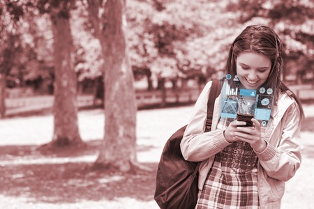 Cheerful young woman texting on her futuristic smartphone in bright park photo