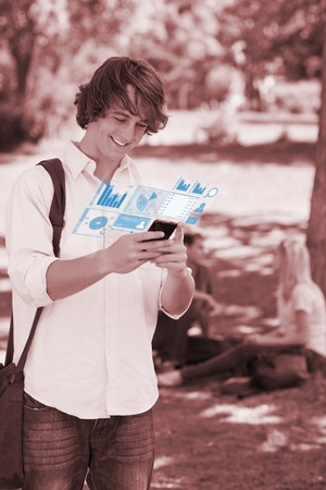 Smiling student working on his digital smartphone in bright park photo