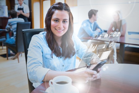 Smiling young woman studying on futuristic smartphone in bright cafe photo