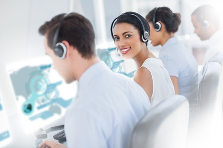 Pretty call center worker using futuristic interface hologram smiling at camera in office photo