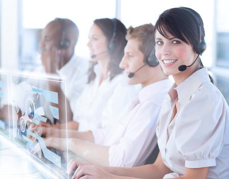 servicio al cliente: Trabajador de centro de llamadas bonita que usa el interfaz futurista hologr�fica sonriendo a la c�mara en la oficina Foto de archivo